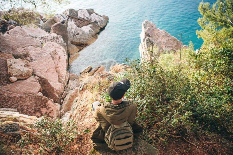 Toerist met een rugzak dichtbij het overzees royalty-vrije stock fotografie