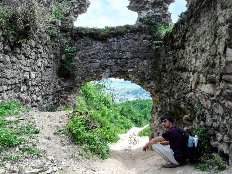 Toerist met een rugzak en zonnebril dichtbij de resten van de Khust-Kasteelpoort die wordt gehurkt Een jonge mens rust dichtbij d stock fotografie