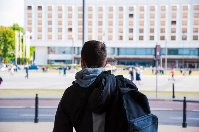 Toerist met rugzak van achter, achtergedeelte Reiziger onder de stad, met lopende vage mensen op de achtergrond stock afbeelding