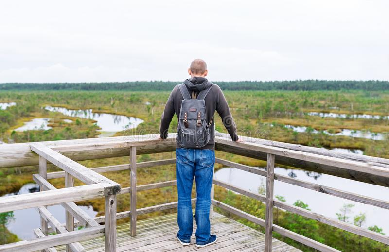 Toerist op brug met rugzak wordt tegengehouden om van aard in de zomerdag te genieten die stock afbeeldingen