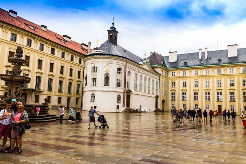 Toeristen bij de tweede binnenplaats van het Kasteel Prazsky van Praag hrad met Kohl Fountain royalty-vrije stock afbeelding
