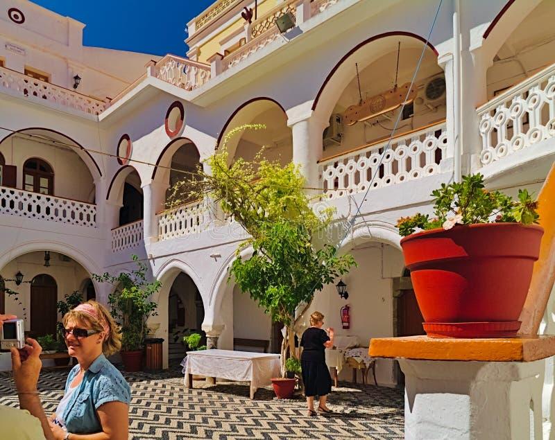 Toeristen bij Panormitis-klooster binnenlandse yard stock foto