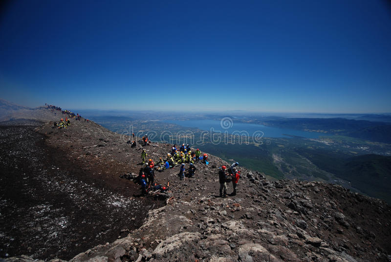 Toeristen bovenop vulkaan stock afbeeldingen