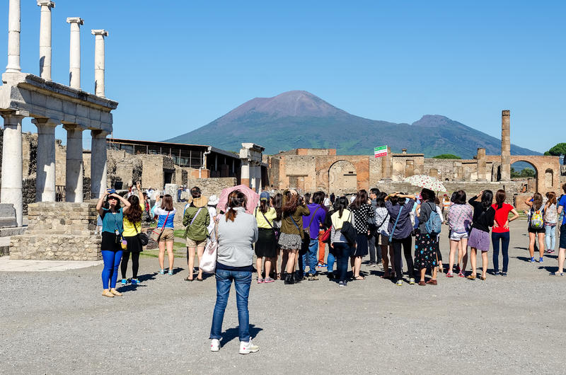 Toeristen in de archeologische plaats van Pompei met binnen de Vesuvius stock foto's