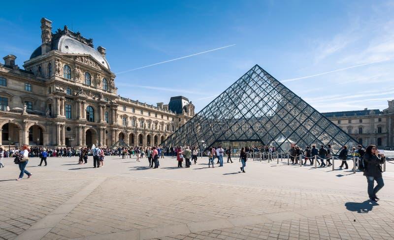 Toeristen in de centrale binnenplaatsen van de Lat met de het Louvrepiramide en paleis stock foto