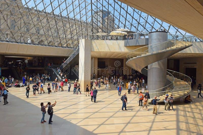 Toeristen in de centrale zaal onder de Lattenpiramide in Parijs stock foto's