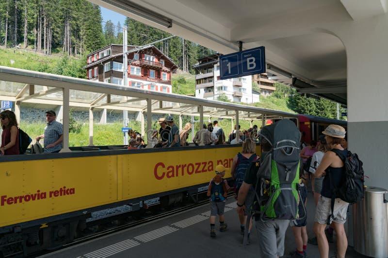Toeristen die aan en uit het open panoramavervoer van de toneel de treinlijn van Chur - van Arosa krijgen in de Zwitserse Alpen stock fotografie