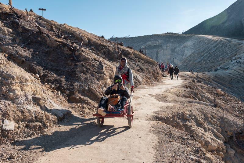 Toeristen die bij de karretjedienst zitten van dorpsbewoner op vulkaan royalty-vrije stock afbeeldingen