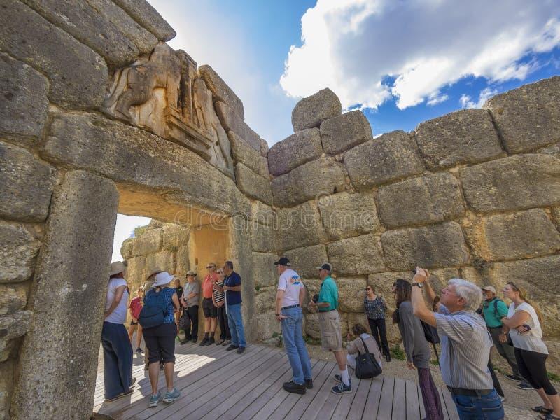 Toeristen die bij de Poort van de Leeuw, Mycenae, Griekenland bezienswaardigheden bezoeken royalty-vrije stock afbeeldingen