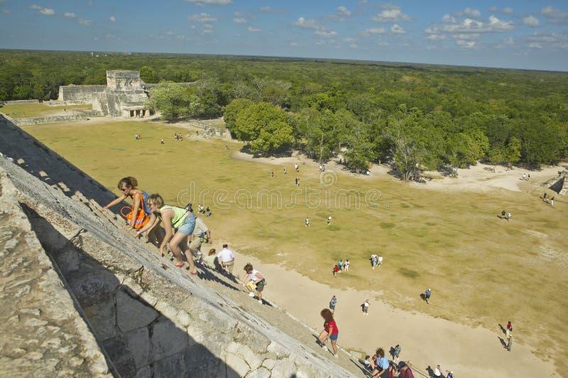 Toeristen die de Mayan Piramide van Kukulkan (ook beklimmen die als El Castillo wordt bekend) en ruïnes in Chichen Itza, het Schi royalty-vrije stock foto's