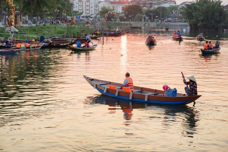 Toeristen die door boten bij zonsondergang reizen Hoi een Oude Stad stock foto
