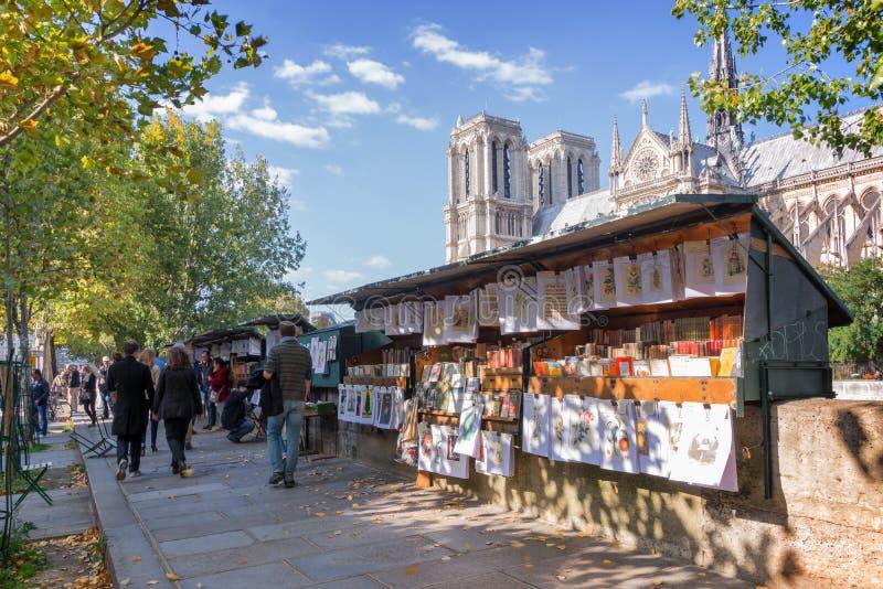 Toeristen die door de dozen van de beroemde boekhandelaar (bouquinistes) lopen langs de Zegenrivier dichtbij Notre Dame in Parijs royalty-vrije stock fotografie