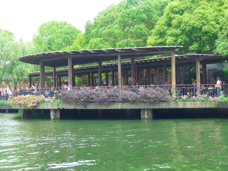 Toeristen die in een groot paviljoen dichtbij een meer rusten stock afbeelding