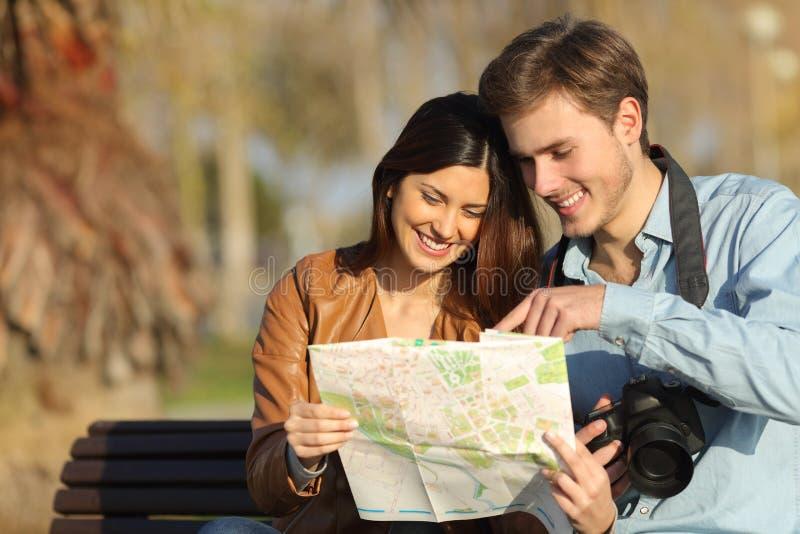 Toeristen die in een kaart in openlucht zoeken stock foto