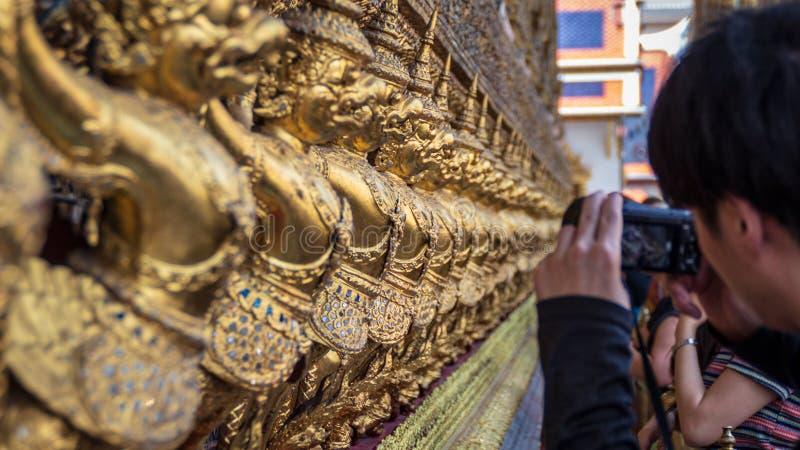 Toeristen die foto van rij van Gouden Garuda-standbeelden in Wat Phra Kaew of de Tempel van Emerald Buddha, Bangkok maken royalty-vrije stock afbeeldingen