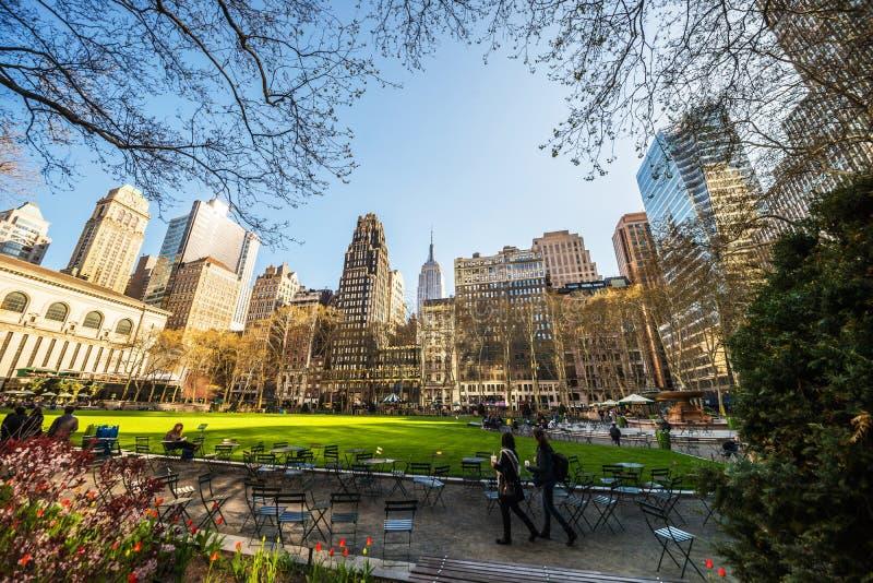 Toeristen die Groene Gazon en Wolkenkrabbers Bryant Park NYC bekijken stock afbeelding