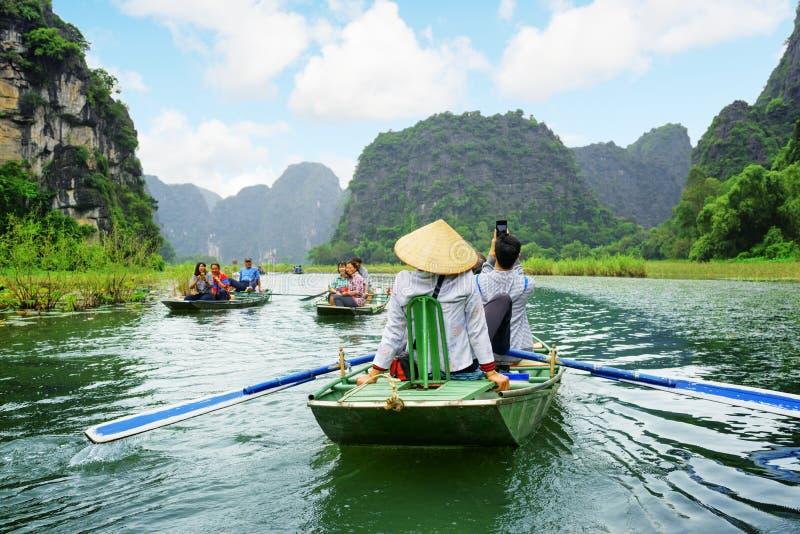 Toeristen die in kleine boot langs Ngo Dong River, Vietnam reizen stock afbeelding