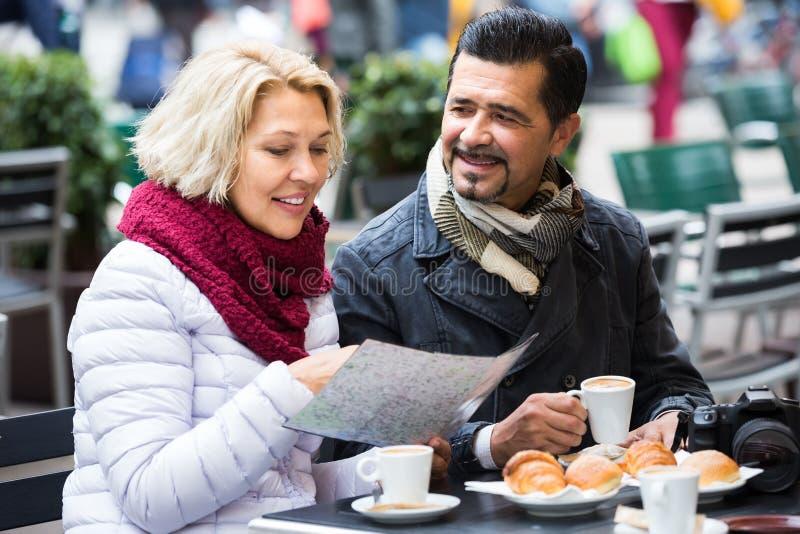 Toeristen die koffie hebben bij koffie en kaart lezen stock foto