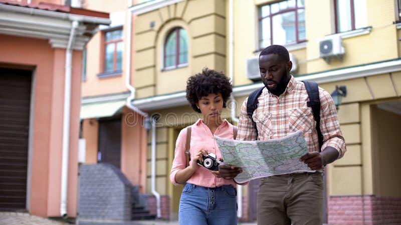 Toeristen die met kaart en fotocamera, richting kiezen, die vakantie reizen stock foto's