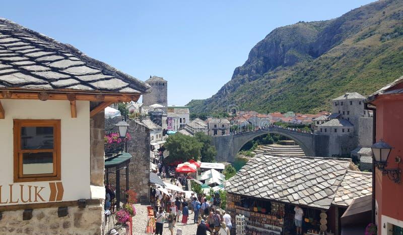 Toeristen die Mostar, historische stad in Bosnië-Herzegovina bezoeken - beroemde Stari de Meeste oude brug op achtergrond royalty-vrije stock afbeeldingen