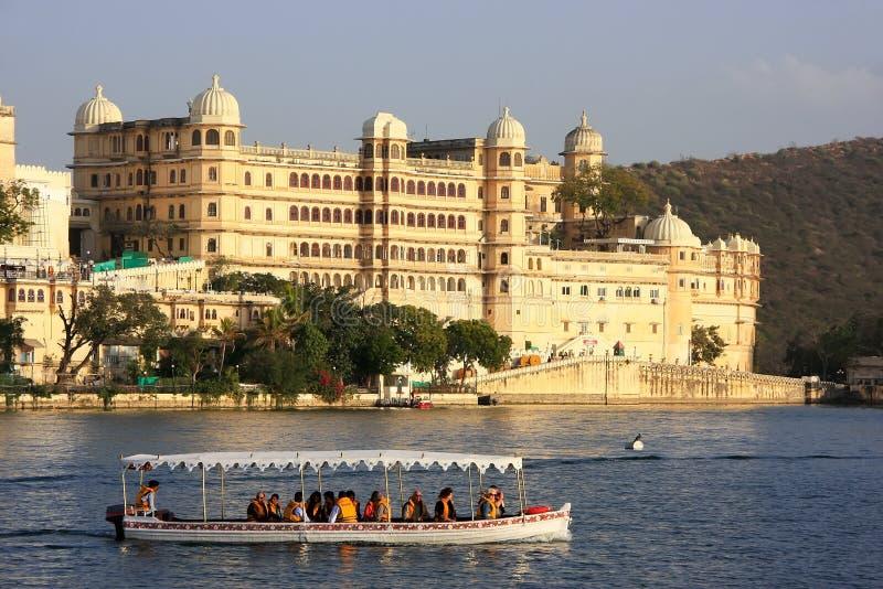 Toeristen die in motorboot voor complex Stadspaleis gaan, Udaipur, India stock foto's