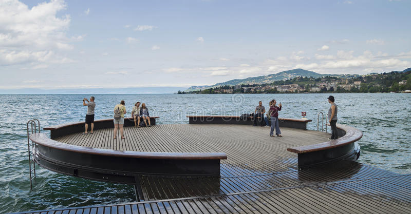 Toeristen die op de kust van het meer ontspannen stock fotografie