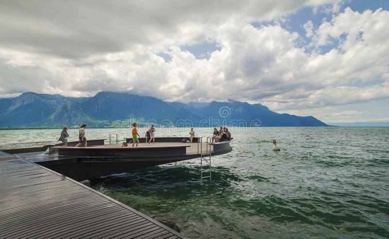 Toeristen die op de kust van het meer ontspannen royalty-vrije stock afbeelding
