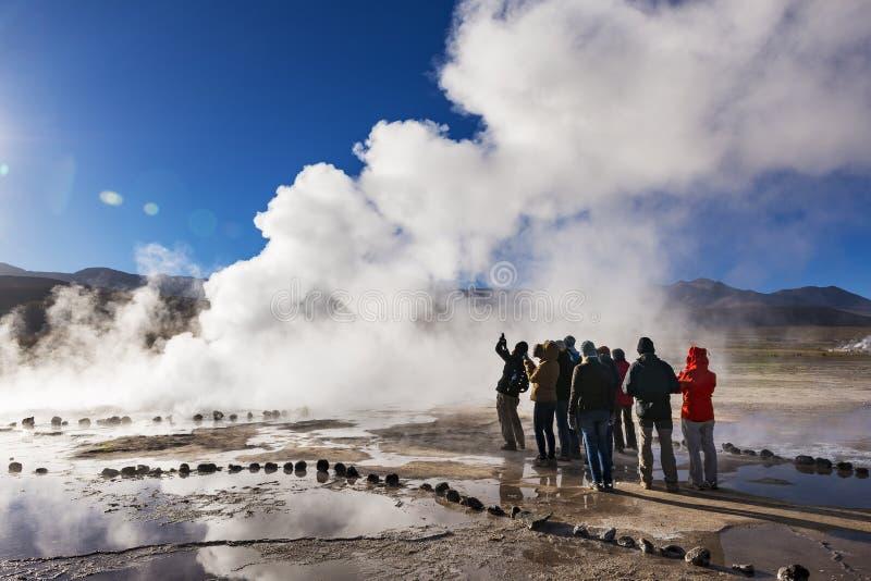 Toeristen die op een geiser op het Geisersdel Tatio gebied letten in de Atacama-Woestijn, Noordelijk Chili stock afbeeldingen