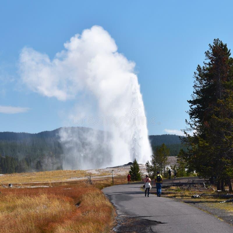 Toeristen die op een uitbarsting van Oude Gelovige Geiser van weg letten, royalty-vrije stock foto