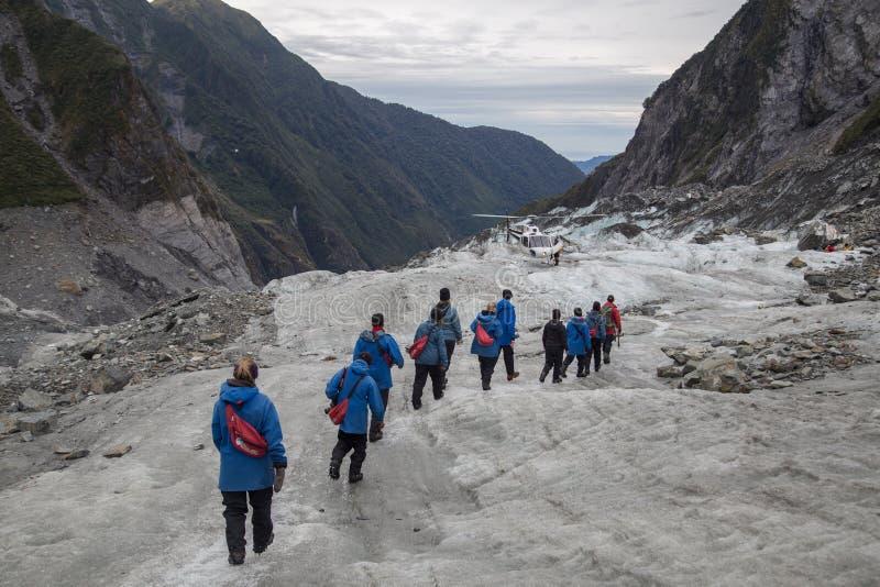 Toeristen die op Franz Josef Glacier, Nieuw Zeeland wandelen stock afbeelding