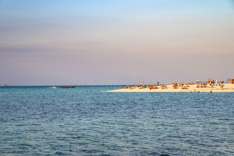 Toeristen die op het strand in tropische overzees bij zonsondergang ontspannen royalty-vrije stock foto