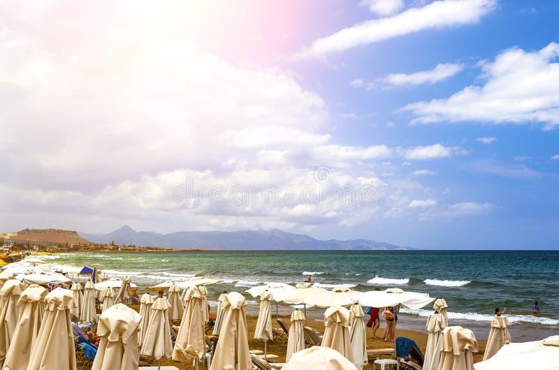 Toeristen die op Strand met meningen langs kustlijn, Kreta, Griekenland, Europa ontspannen stock afbeelding