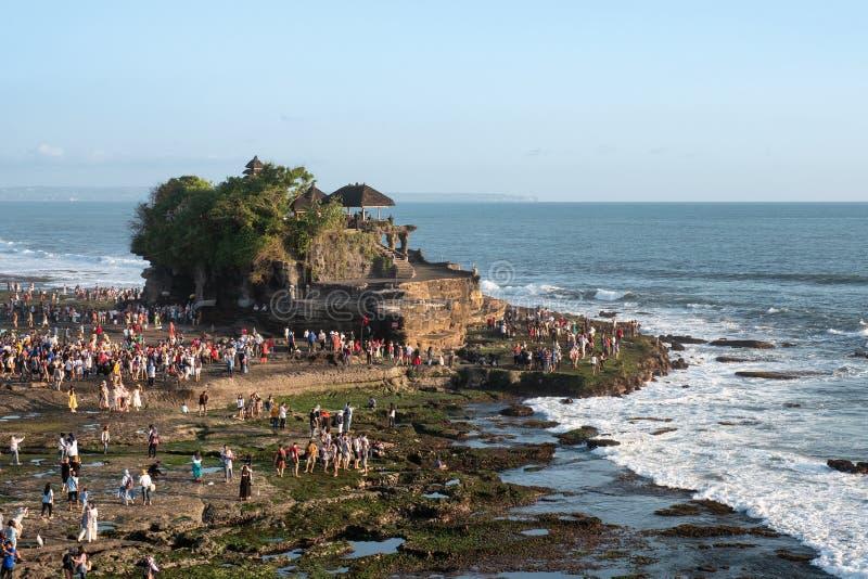 Toeristen die op vakantie bij Tanah-Partijtempel reizen op kustlijn stock foto's