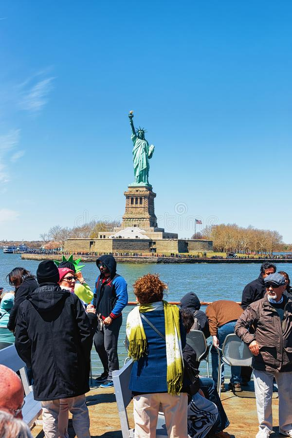 Toeristen die op veerboot Liberty Island en Standbeeld de V.S. bekijken stock foto's