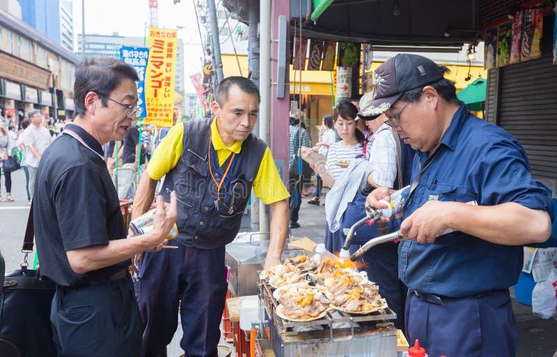 Toeristen die snack van straatventer op de kokende zeevruchten letten stock afbeelding