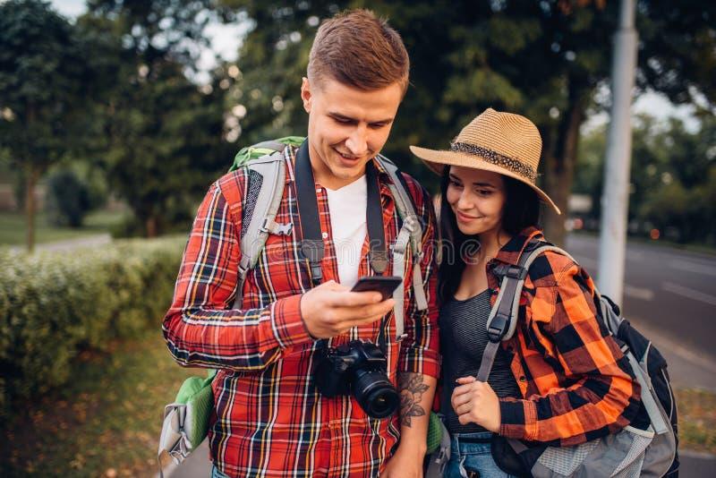 Toeristen die stadsaantrekkelijkheden op navigator zoeken stock foto's