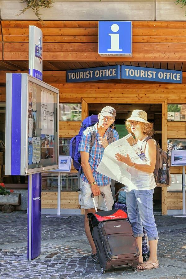 Toeristen die stadskaart onderzoeken bij toerist offcie van Zermatt stock afbeelding