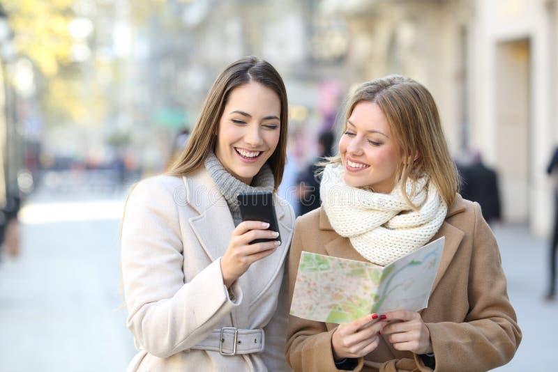 Toeristen die telefoon en kaart in de wintervakantie vergelijken stock fotografie