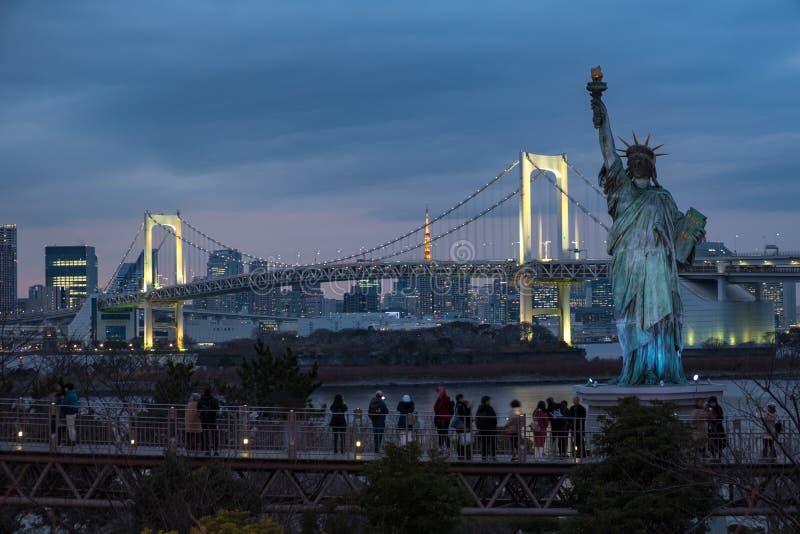 Toeristen die van mening van Japans standbeeld van vrijheid en regenboogbrug genieten bij blauw uur royalty-vrije stock afbeelding