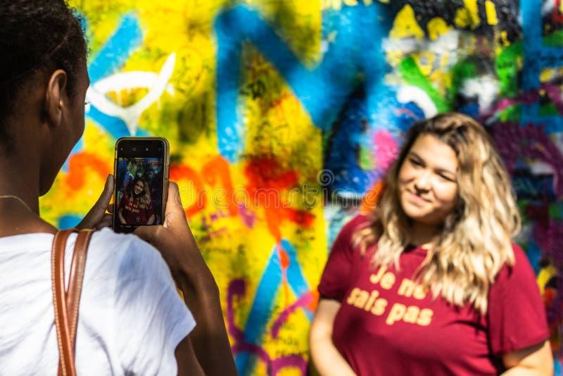 Toeristen die voor Lennon Wall in Praag fotograferen stock afbeeldingen