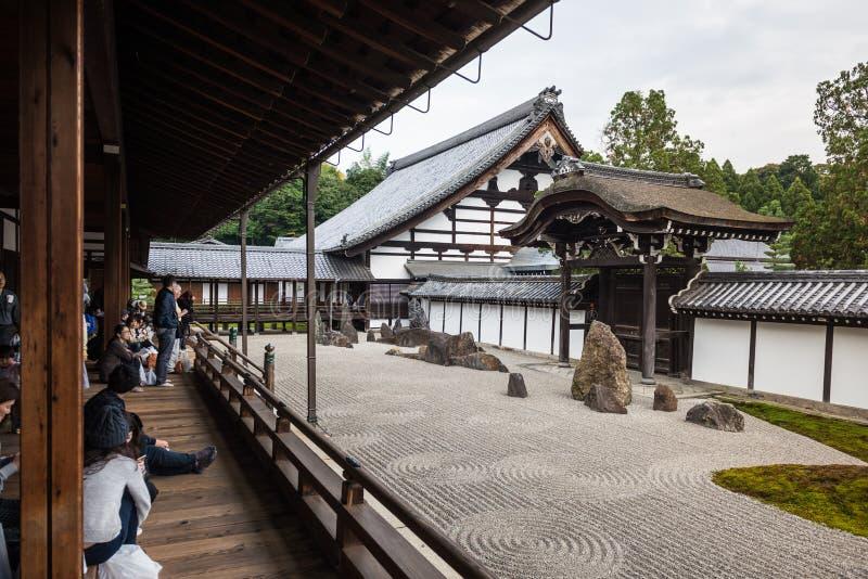 Toeristen die zen de tuin van de steenkiezelsteen kijken stock foto