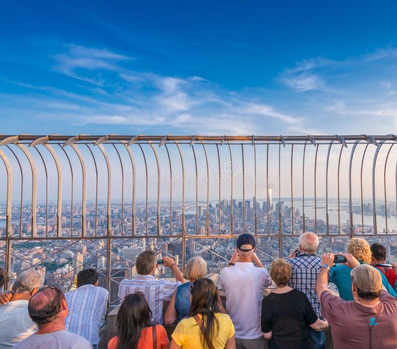 Toeristen door de zonsonderganghorizon die van New York worden verbaasd stock afbeelding