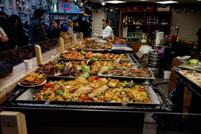 Toeristen en plaatselijke bevolking die van Hongaars straatvoedsel genieten bij Kerstmismarkt royalty-vrije stock afbeeldingen