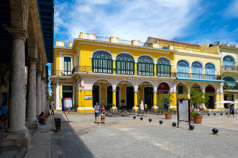 Toeristen en plaatselijke bewoners bij een kleurrijk vierkant op Oud Havana stock fotografie