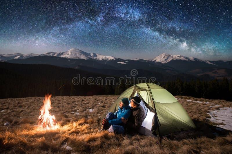 Toeristen in het kamperen bij nacht, die een rust hebben dichtbij kampvuur en tent onder het hoogtepunt van de nachthemel van ste stock fotografie