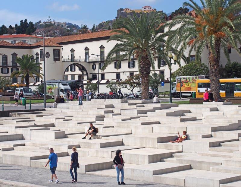 Toeristen het zitten en passers langs op de concrete stappen van de jachthaven in Funchal die de oude stad met historische gebouw royalty-vrije stock afbeeldingen