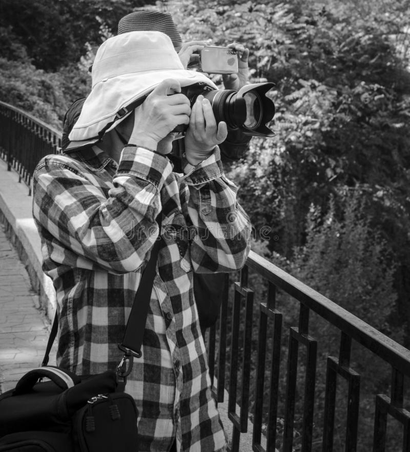 Toeristen in hoeden die lokale oriëntatiepunten fotograferen stock foto's