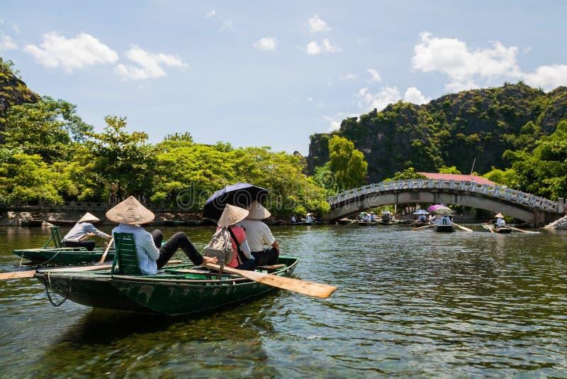 Toeristen in houten boten om Tam Coc te reizen royalty-vrije stock foto