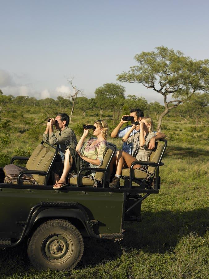 Toeristen in Jeep Looking Through Binoculars royalty-vrije stock afbeelding