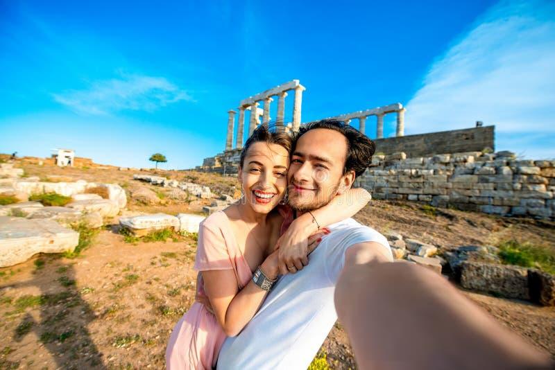 Toeristen jong paar dichtbij Poseidon-tempel in Griekenland royalty-vrije stock foto's